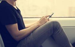 Giovane che utilizza uno smartphone in un treno o in un sottopassaggio Fotografia Stock