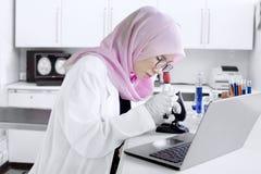 Giovane chimico che lavora con il microscopio Immagine Stock