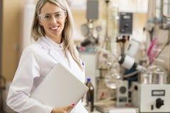 Giovane chimico con il computer portatile che sta nel laboratorio di chimica Immagine Stock