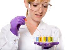 Giovane chimico femminile che effettua una certa ricerca, isolata Fotografie Stock