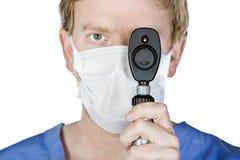 Giovane chirurgo con l'indicatore luminoso della holding della mascherina fino al suo occhio Fotografie Stock