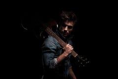 Giovane chitarrista drammatico che guarda indietro mentre tenendo chitarra su SH Immagini Stock