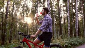 Giovane ciclista che si siede sulla sue bicicletta ed acqua potabile archivi video