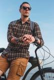 Giovane ciclista maschio con la bicicletta che riposa vicino al mare Concetto urbano di estate di rilassamento di stile di vita d Fotografia Stock