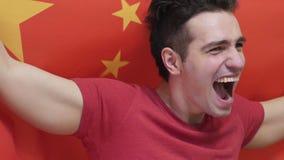 Giovane cinese che celebra mentre tenendo la bandiera cinese al rallentatore video d archivio