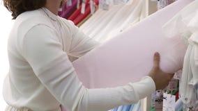 Giovane cliente femminile che cerca il tessuto nel negozio del tessuto Scelta di quello rosa-chiaro Vista laterale archivi video
