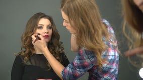 Giovane cliente femminile che guarda nello specchio mentre truccatore che lavora alla sua pelle di tono nel salone di bellezza archivi video
