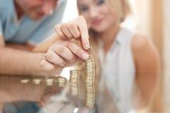 Giovane colonna dei soldi della costruzione delle coppie dalle monete immagine stock