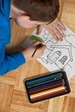 Giovane coloritura del ragazzo sul pavimento Immagini Stock