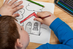Giovane coloritura del ragazzo sul pavimento Immagine Stock
