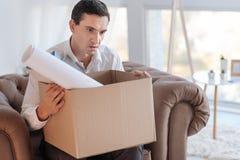 Giovane colpito che si siede con una scatola dopo la perdita del suo lavoro Immagine Stock Libera da Diritti
