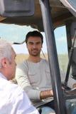 Giovane coltivatore che comunica con uomo più anziano Immagine Stock Libera da Diritti