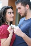 Giovane combattimento delle coppie, discutente sui soldi Immagine Stock
