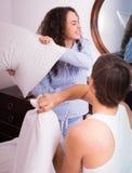 Giovane combattimento felice delle coppie sui cuscini a letto Fotografia Stock