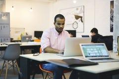Giovane computer dello studente e dell'insegnante mentre lavorando nell'ufficio moderno facendo uso di Internet senza fili Fotografia Stock