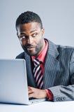 Giovane computer portatile afroamericano di Being Sneaky On dell'uomo d'affari Immagini Stock Libere da Diritti