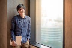 Giovane computer portatile asiatico della tenuta dell'uomo Immagini Stock
