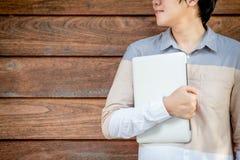 Giovane computer portatile asiatico della tenuta dell'uomo dello studente universitario Fotografia Stock Libera da Diritti