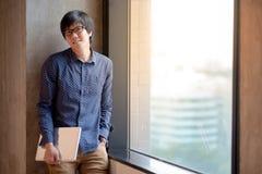 Giovane computer portatile asiatico della tenuta dello studente universitario dell'uomo Fotografie Stock Libere da Diritti