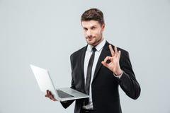 Giovane computer portatile attraente della tenuta dell'uomo d'affari e segno giusto di rappresentazione Fotografia Stock