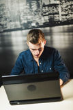 Giovane computer portatile attraente di uso dell'uomo Immagine Stock