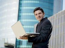 Giovane computer portatile del computer della tenuta dell'uomo d'affari che funziona affare urbano all'aperto Immagine Stock Libera da Diritti