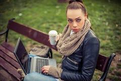 Giovane computer portatile di Using dello studente in parco Immagini Stock
