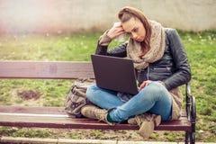 Giovane computer portatile di Using dello studente in parco Fotografia Stock