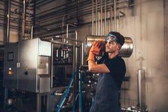 Giovane con i barilotti di birra del metallo alla fabbrica di birra Fotografia Stock