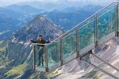 Giovane con i pollici su alle montagne dell'austriaco della piattaforma di vista Immagini Stock