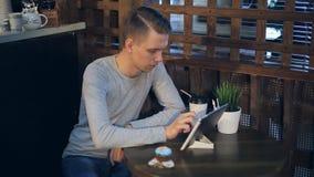 Giovane con il caffè bevente del computer della compressa in caffè archivi video