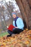 Giovane con il cappello e la sciarpa che legge un libro Fotografie Stock Libere da Diritti