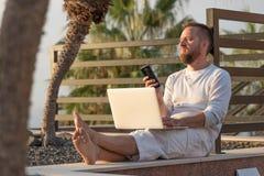 Giovane con il computer portatile al tramonto fotografia stock