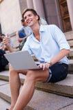 Giovane con il computer portatile all'aperto Immagine Stock