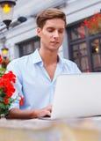Giovane con il computer portatile all'aperto Fotografia Stock