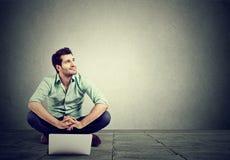 Giovane con il computer portatile che si siede sul pavimento Fotografie Stock