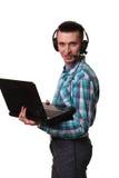Giovane con il computer portatile della tenuta della cuffia avricolare - uomo della call center con il hea Fotografie Stock