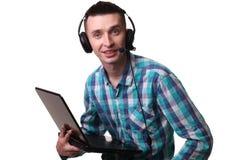 Giovane con il computer portatile della tenuta della cuffia avricolare - uomo della call center con il hea Immagine Stock