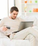 Giovane con il computer portatile e la carta di credito a casa Fotografia Stock