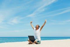 Giovane con il computer portatile sulla spiaggia Immagini Stock Libere da Diritti
