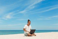 Giovane con il computer portatile sulla spiaggia Immagine Stock Libera da Diritti