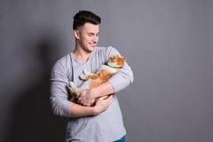 Giovane con il gatto dello zenzero al fondo grigio dello studio Fotografie Stock Libere da Diritti