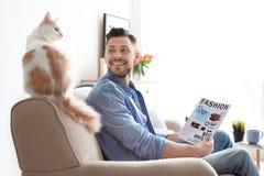 Giovane con il gatto sveglio sul sofà fotografia stock