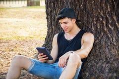 Giovane con il lettore Relaxing del libro elettronico o della compressa a Immagine Stock