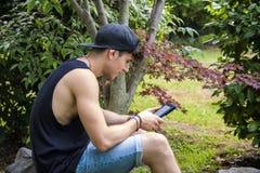 Giovane con il lettore Relaxing del libro elettronico o della compressa a Immagini Stock
