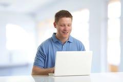 Tipo felice che per mezzo del suo computer portatile Immagine Stock