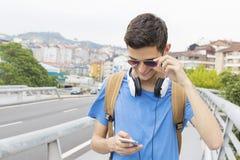 Giovane con il telefono cellulare sulla via Immagine Stock