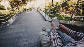 giovane con il telefono in sua mano che si siede sui punti Vista superiore Immagini Stock Libere da Diritti
