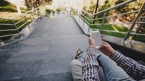 giovane con il telefono in sua mano che si siede sui punti Vista superiore Fotografia Stock Libera da Diritti