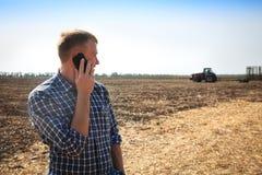 Giovane con il telefono in un campo e un trattore su un fondo Immagini Stock